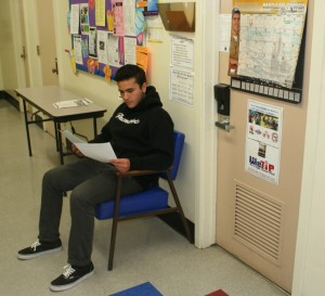 Student waits outside the school counselor's office to discuss AP Testing options. They read literature concerning the multple tests they have the choice of taking, payment options and parent-student contracts.